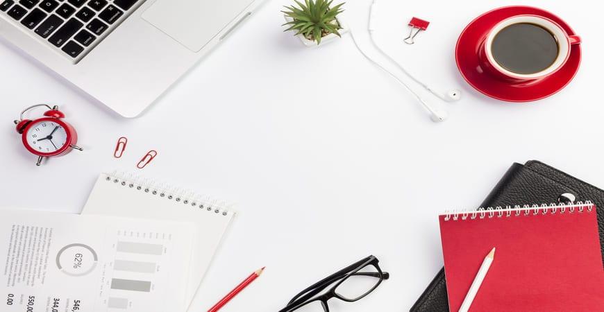 Escritorio con cuaderno y taza rojos